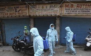 Des agents pulvérisent du désinfectant sur un marché de pièces de rechange automobile à New Delhi, le 18 mai 2020.