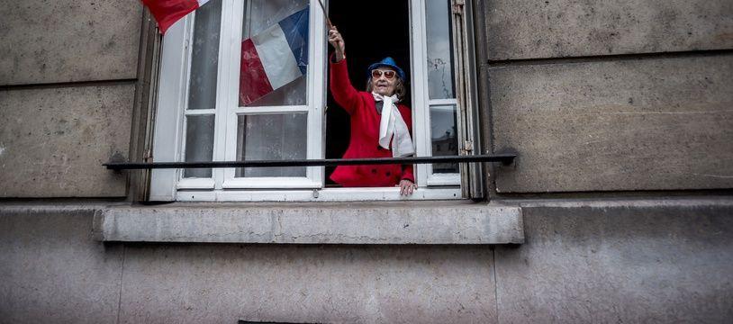 Une femme rend hommage aux soignants avec un drapeau français, le 10 mai 2020.