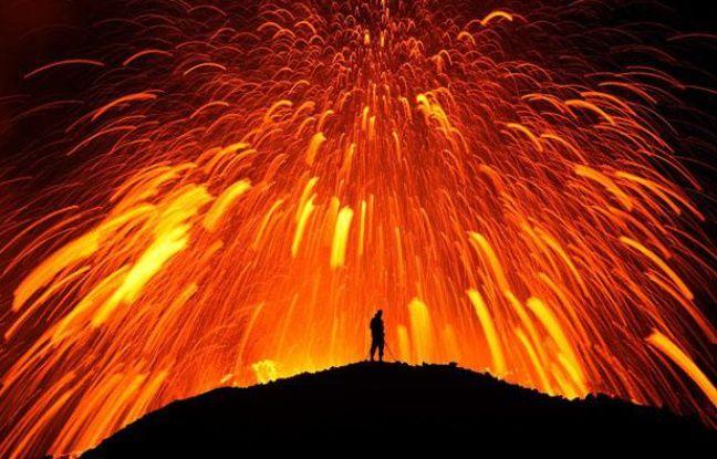 Un homme face à l'explosion d'un volcan, dans le glacier islandais Fimmvorduhals, près de Reykjavik, le 15 mai 2011