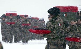 Les honneurs militaires aux quatre soldats français tombés vendredi en Afghanistan ont été rendus sous la neige dimanche, avant que les cercueils des défunts ne soient embarqués dans l'avion du ministre de la Défense Gérard Longuet pour arriver dans la soirée à Paris.