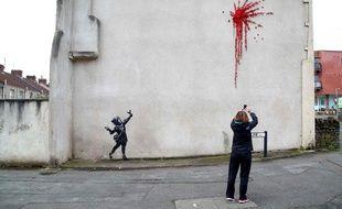 Une passante photographie la nouvelle œuvre de Banksy à Bristol, le 14 février 2020.