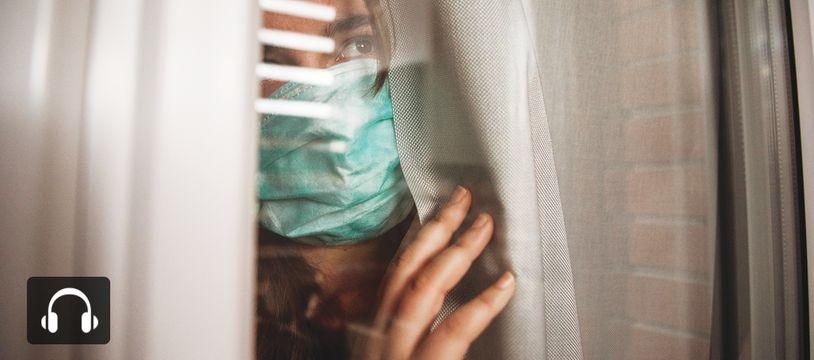 Une jeune femme inquiète regarde par la fenêtre.