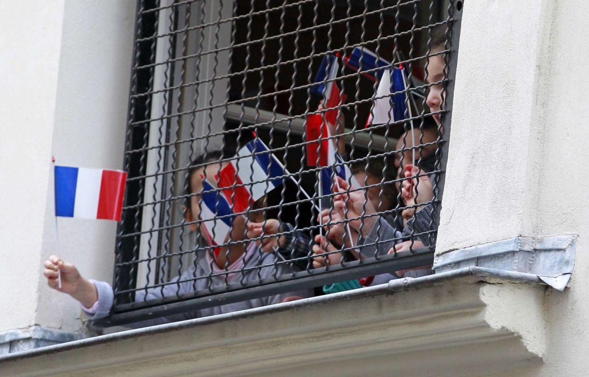 Des enfants affichent des drapeaux français à la fenêtre d'une école juive, au coeur de Paris pendant la visite de Bernard Cazeneuve. – Remy de la Mauviniere/AP/SIPA