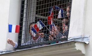 Des enfants affichent des drapeaux français à la fenêtre d'une école juive, au coeur de Paris pendant la visite de Bernard Cazeneuve.
