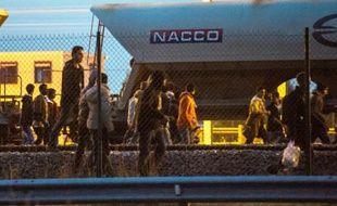 Des migrants marchent sur la voie ferrée en direction du terminal d'Eurotunnel le 11 août 2015 à Fréhun