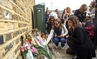 Des jeunes filles au pair déposent des fleurs devant la maison où le corps de Sophie Lionnet a été retrouvé.