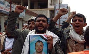 Des supporteurs des rebelles chiites, les houthis, brandissent les portraits de membres tués dans une attaque suicide cinq jours auparavant à Sanaa le 14 octobre 2014
