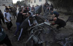 Des Palestiniens se rassemblent autour d'une voiture après qu'elle a été frappée par une frappe aérienne israélienne, à Gaza, samedi 15 mai 2021.