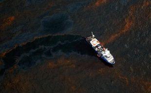 Le 28 avril 2010, un bateau est au milieu de la nappe de pétrole due à l'explosion de la platerforme pétrolière Deepwater, dans le Golfe du Mexique.