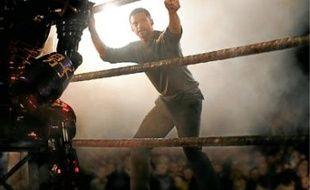 Hugh Jackman donne des instructions à un robot-boxeur.