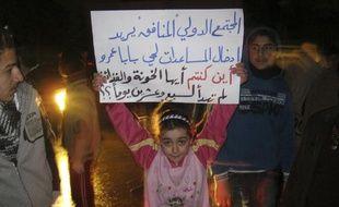Une petite fille tient une pancarte de protestation contre le régime de Bachar al-Assad, le 3 mars 2012, à Homs (Syrie).