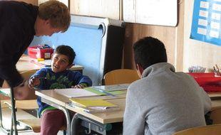 Des migrants avec un enseignant bénévole à Grande Synthe