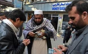 Des changeurs de devises comptent leurs billets dans le marché de Shahzada à Kaboul, le 29 décembre 2014
