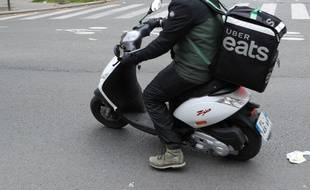 Un livreur Uber Eats en scooter