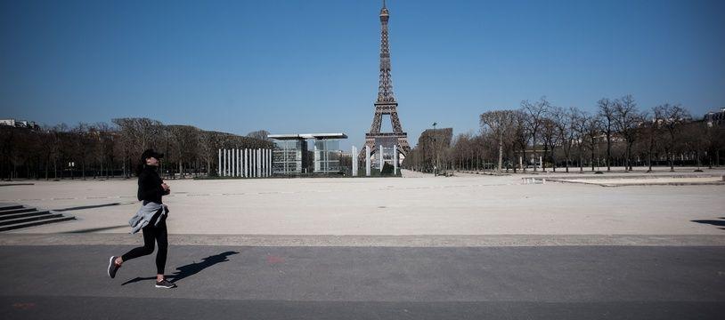 Une femme faisant son jogging, autour du Champs de Mars, à Paris, non loin de la Tour Eiffel.