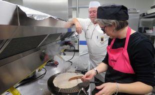 Marie-Hélène apprend à bien étaler la pâte sur le bilig, sous l'œil bienveillant de son formateur.