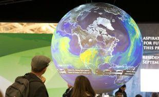 Des visiteurs regardent le globe terrestre au Bourget lors de la conférence sur le climat, le 10 décembre 2015