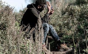 Calais (Pas-de-Calais), le 31 octobre 2016. Un migrant regarde son smartphone dans la «Jungle» de Calais.