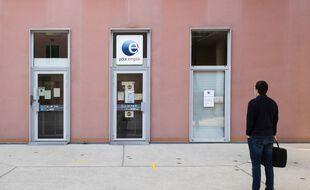 Un homme devant une agence Pôle Emploi.