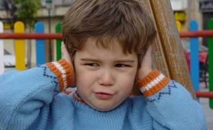 Un petit garçon se bouche les oreilles à cause du bruit (illustration).