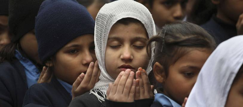 Pakistani students pray during a special ceremony for the victims of Tuesday's school attack in Peshawar, at a school in Lahore, Pakistan, Wednesday, Dec. 17, 2014. Pakistan is mourning as the nation prepares for mass funerals for over 140 people, most of them children, killed in a Taliban attack on a military-run school in the country's northwest. (AP Photo/K.M. Chaudary)/ISL102/233385354127/1412170904