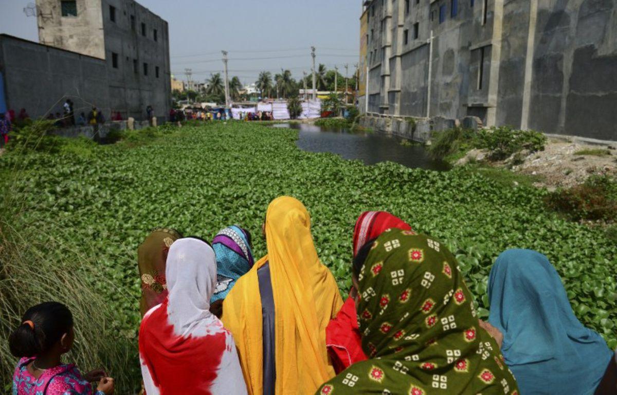 Des bangladais se rassemblent devant le lieu où se tenait l'immeuble Rana Plaza, qui s'est effondré sur plus d'un millier d'ouvriers textiles. – MUNIR UZ ZAMAN / AFP