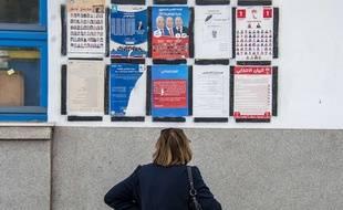 Une Tunisienne dans les rues de Tunis regarde les panneaux électoraux, le 5 mai 2018.