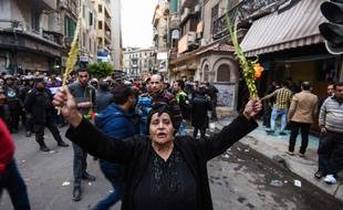 Une Egyptienne copte brandit des feuilles de palmiers, après l'attentat contre un lieu de culte à Alexandrie, en pleine cérémonie des Rameaux.