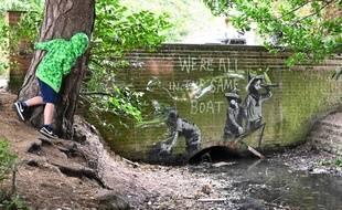 Banksy a réalisé une peinture au pochoir de trois enfants sur une barque de tôle ondulée reposé contre un mur de briques, avec l'inscription «We're all in the same boat», faisant écho à la crise environnementale.