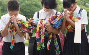 Des écoliers prient en hommage aux victimes de la bombe atomique lancée en 1945, à Hiroshima le 6 août 2014