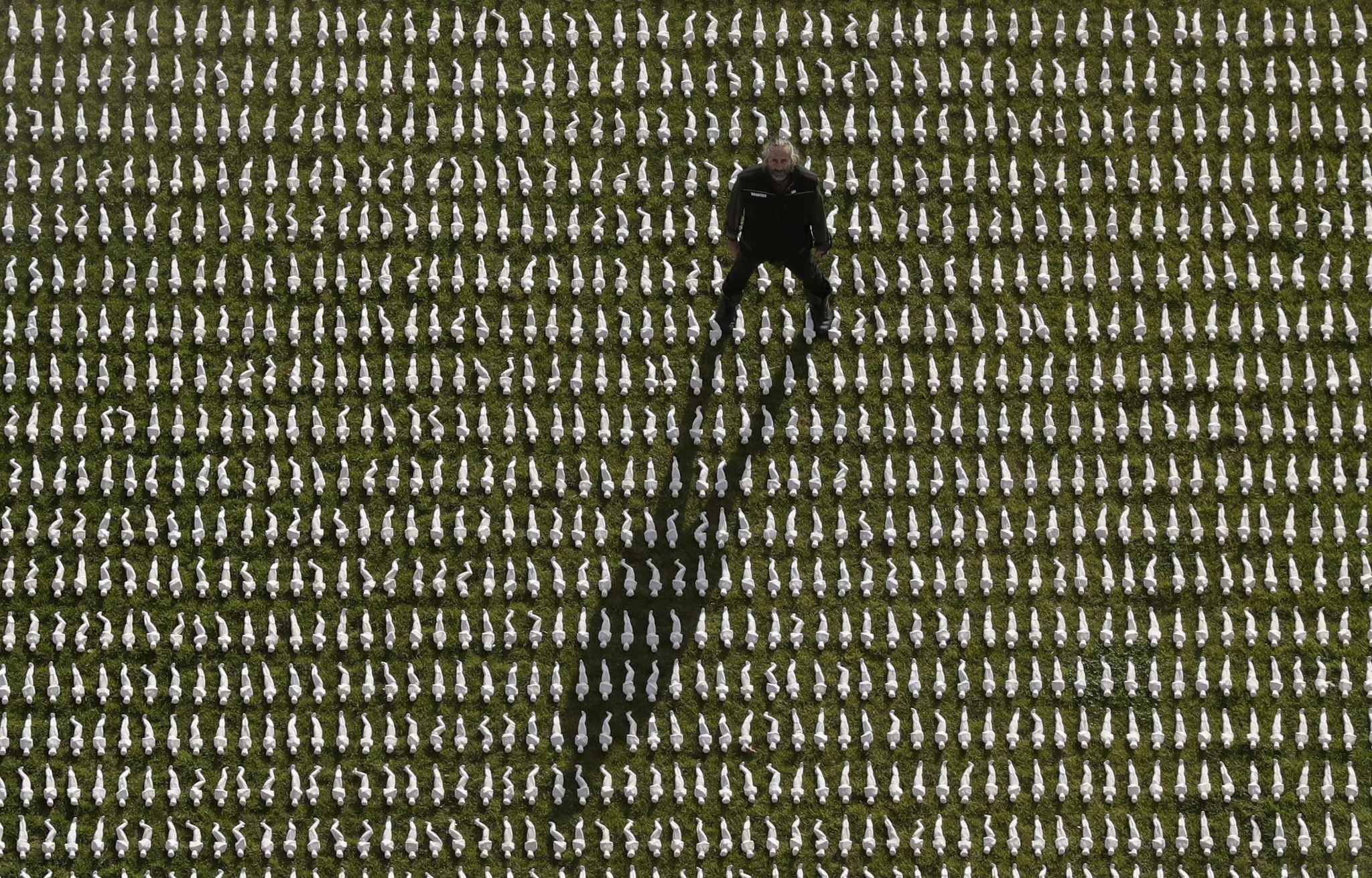 British artist Rob Heard poses for photographs amongst rows of 72,396 shrouded figures which form his piece of commemorative art 'Shrouds of the Somme' to mark the upcoming centenary of the end of World War I, in the Queen Elizabeth Olympic Park, London, Wednesday, Nov. 7, 2018. Each figure is a human form, individually shaped, shrouded and made to a name of the 72,396 missing British and Commonwealth servicemen who were killed fighting in the Somme area of France between July 1, 2016 and March 20, 1918 who have no known grave and whose names are engraved on the Thiepval Memorial in France. World War I ended on November 11, 1918.