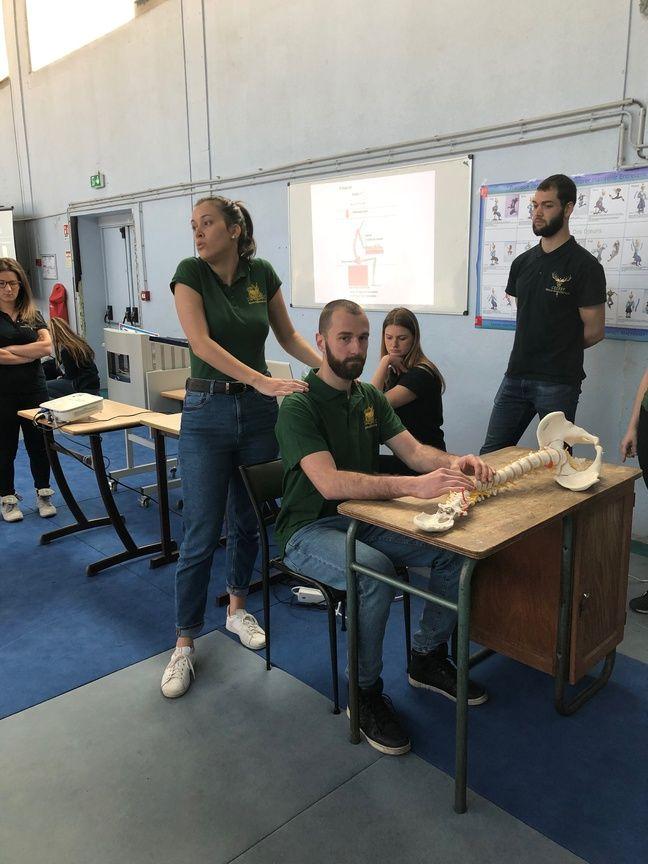 Ces étudiants en kiné montrent avec un squelette en mimant les mouvements les postures à éviter et les étirements à pratiquer.