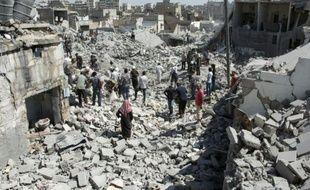 Des habitants d'Alep dans les décombres d'immeubles après des tirs de missiles par le gouvernement syrien, le 21 juillet 2015