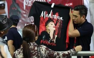 Des Philippins achètent des t-shirts de Madonna à l'occasion d'un concert de la star à Manille, le 24 février 2016.
