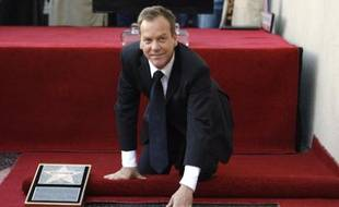 Actor Kiefer Sutherland touches his star on the Walk of Fame in Hollywood, California December 9, 2008. Sutherland was the 2,377th celebrity to be honored with a star on the Walk of Fame. REUTERS/Mario Anzuoni (UNITED STATES)