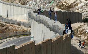 Des Palestiniens debout sur le mur séparant la ville d'Abu Dis en Cisjordanie et Jérusalem est le 28 octobre 2015