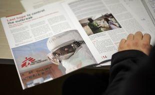 Un journaliste lit le rapport intitulé «Poussés au-delà de nos limites», et publié ce lundi par Médecins Sans Frontières (MSF), à Genève, le 23 mars 2015. AFP PHOTO / FABRICE COFFRINI