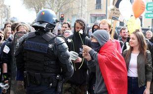 Des opposants à la loi Travail donnent des fleurs à un gendarme, ici lors d'une manifestation à Rennes le 5 avril 2016.