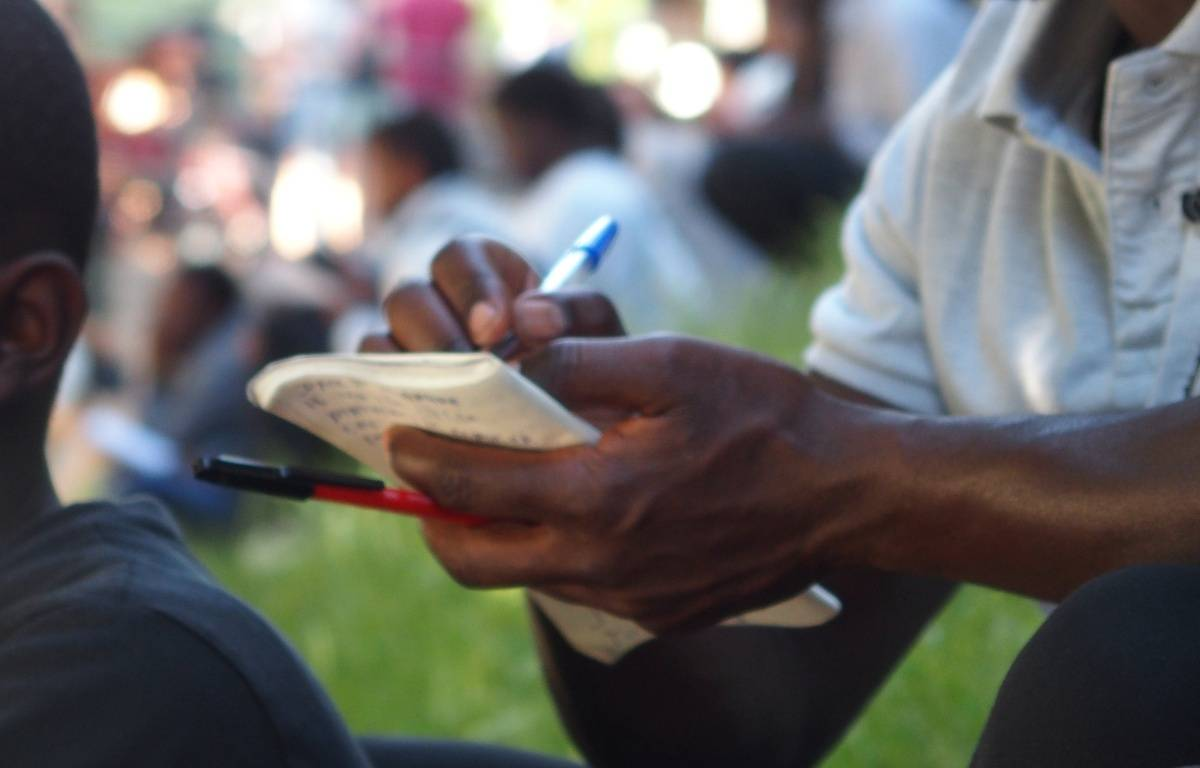 Paris, le 14 juin 2017. Des bénévoles permettent à des migrants d'écouter, écrire, lire et répéter des expressions françaises pour des cours d'alphabétisation improvisés sur la rotonde de la Villette.  – C.ANGER