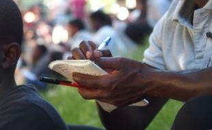 Paris, le 14 juin 2017. Des bénévoles permettent à des migrants d'écouter, écrire, lire et répéter des expressions françaises pour des cours d'alphabétisation improvisés sur la rotonde de la Villette.