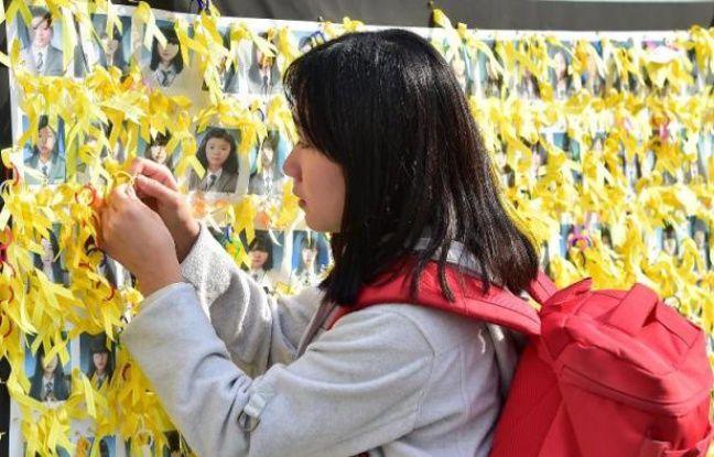 Une jeune femme attache un ruban jaune sur les portraits des victimes du naufrage du ferry sud-coréen Sewol, le 15 octobre 2014 à Séoul