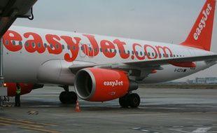 Illustration avion Easyjet a l'arrivee a l'aeroport Toulouse Blagnac. Logo manoeuvres dechargement des bagages. Compagnie low cost Easy jet.