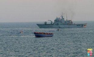 Un bateau de la Marine italienne s'approche d'une embarcation en difficulté remplie de migrants, le 2 avril 2014 en Méditerranée