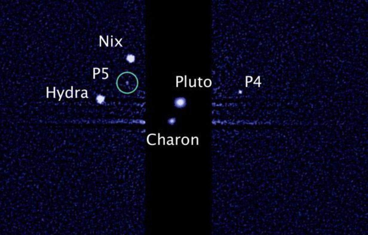 Image capturée par le téléscope Hubble des cinq lunes gravitant autour de Pluton, le 7 juillet 2012. – AFP PHOTO / NASA / ESA
