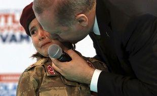 Le président turc Recep Tayyip Erdogan, embrassant une petite fille qui a revêtu la tenue militaire turque, lors d'un congrès de l'AKP le 24 février 2018.