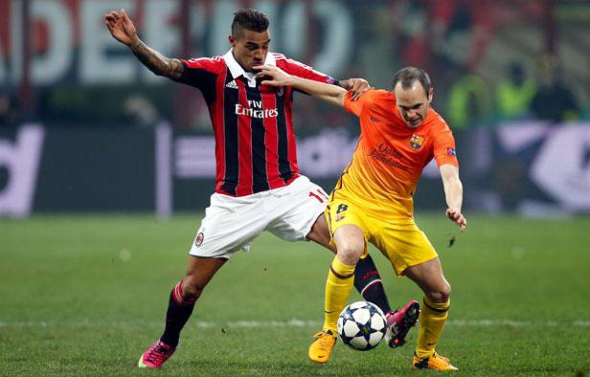 Le Milanais Kevin Prince-Boateng à la lutte avec le Barcelonais Andres Iniesta le 20 février 2013. – REUTERS/Tony Gentile