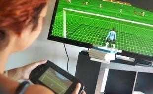 Une joueuse joue à un célèbre jeu vidéo de football (Illustration).