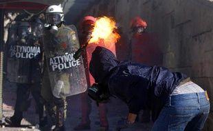Un manifestant jette un cocktail molotov sur des policiers à Athènes, le 19 octobre 2011.