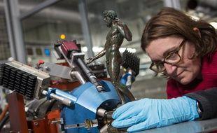 Une scientifique place une statuette de bronze pour analyse devant Aglaé.