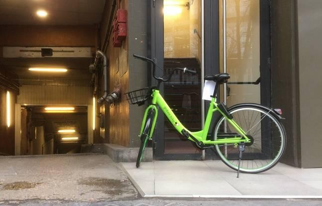 Un Gobee Bike posé dans Paris sur un trottoir et devant une porte. (Illustration)
